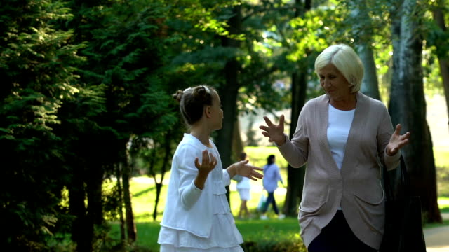 Little-girl-walking-with-granny-and-telling-her-stories-from-school-life-trust
