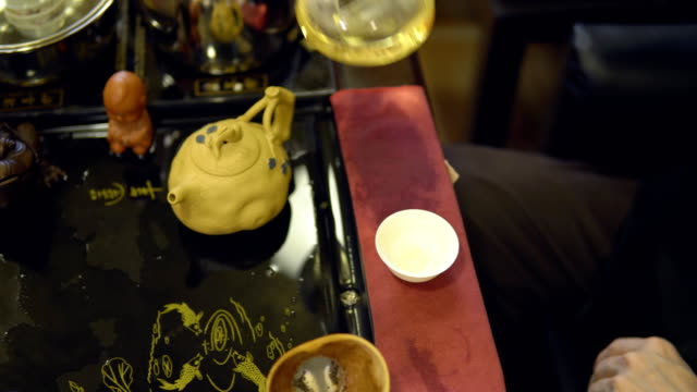 Tea-ceremony-Master-pours-green-tea-from-a-glass-teapot-into-a-white-mug