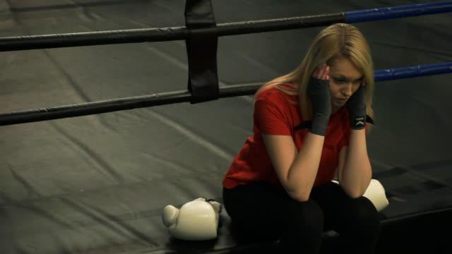 Joven-cansada-sentado-en-el-ring-después-del-entrenamiento