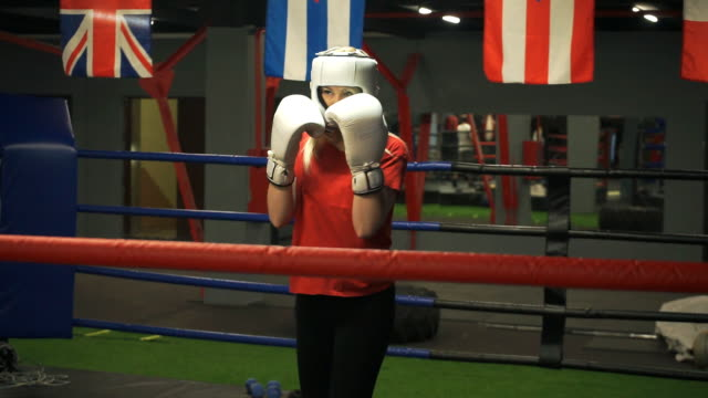Young-girl-in-a-helmet-and-gloves-is-training-blows