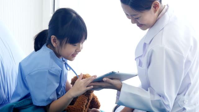 Médico-a-la-niña-en-el-Hospital,-la-niña-mirando-a-tablet-con-doctor-junto-en-el-hospital.-Personas-con-la-tecnología,-concepto-de-salud-y-médico.