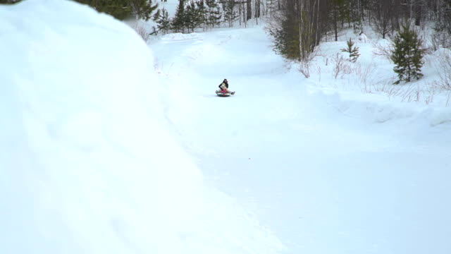 Girl-and-Woman-Riding-Fast-on-a-Snow-Tubing