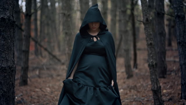Black-witch-in-hood-walks-in-autumn-scary-forest-Womanl-in-long-dress-Halloween-horror-concept-cosplay-dressing-up