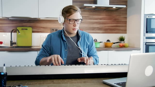 Young-man-learning-synthesizer-watching-at-online-lessons-on-laptop-computer