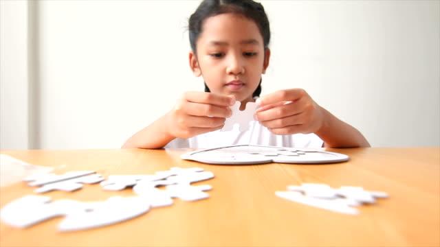 Asiatische-kleine-Mädchen-spielen-Puzzle-Puzzle-wählen-Sie-konzentrieren-sich-auf-Hand-geringe-Schärfentiefe