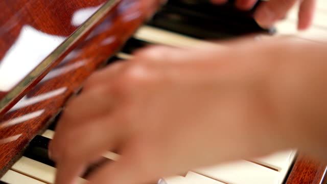 Female-fingers-playing-keys-on-retro-piano-keyboard-Shallow-depth-of-field-Focus-on-piano-keys