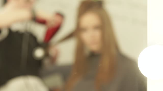 Blurred-reflection-in-mirror-hairdresser-making-woman-hairstyling-long-hair-with-dryer-and-brush-in-beauty-salon-Hairstyling-fashion-model-in-dressing-room