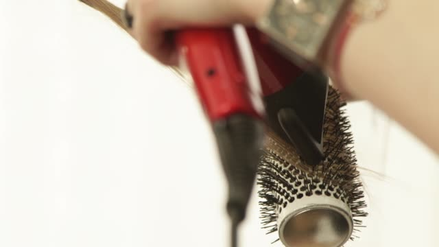 Haircutter-using-dryer-and-hairbrush-for-drying-and-styling-long-hair-after-hairdressing-in-beauty-studio-Close-up-haircutter-finish-hairstyling-after-haircut-in-hairdressing-salon