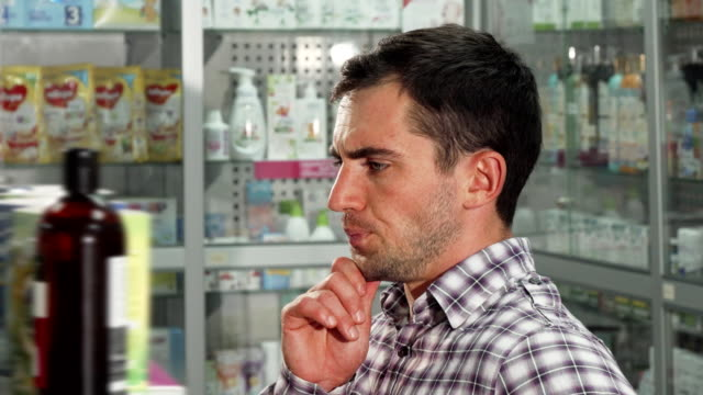 Handsome-man-examining-goods-for-sale-at-the-pharmacy