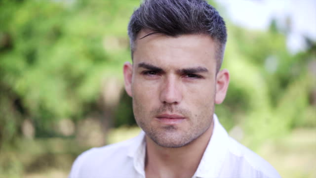 Portrait-of-the-Attractive-man-who-looks-seriously-at-the-camera-On-the-green-nature-Background-Close-up
