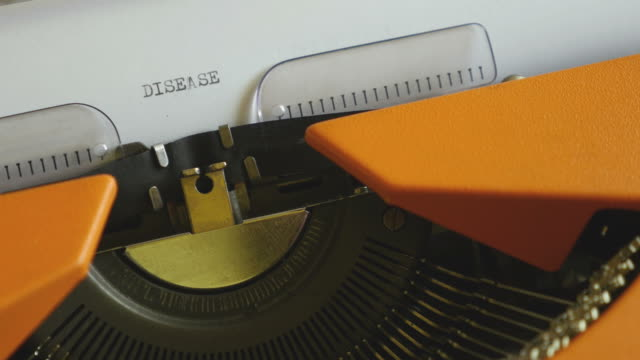 High-and-side-angle-footage-of-a-person-writing-DISEASE-on-an-old-typewriter-with-sound