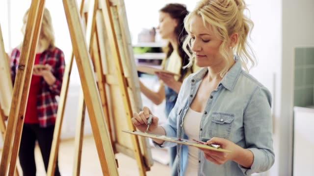estudiantes-con-caballetes-de-pintura-en-la-escuela-de-arte