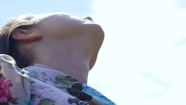 Frau-mit-geschlossenen-Augen-Kopf-bis-zum-Himmel-zu-beten-mit-Blick-auf-Himmel-langsam-hob