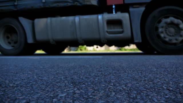 LKW-fährt-auf-einer-asphaltierten-Straße-Verschwommene-Auto-fährt-an-der-Autobahn-an-der-sonnigen-Sommertag-Niedrigen-Winkel-Ansicht-schließen-Slow-motion
