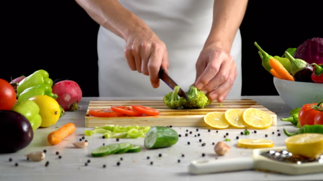 Chef-is-cutting-broccoli-in-the-kitchen