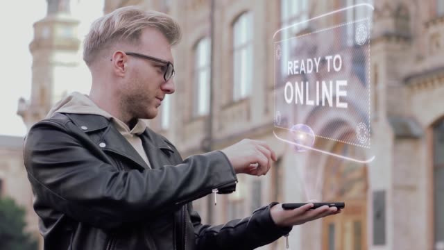 Smart-young-man-with-glasses-shows-a-conceptual-hologram-Ready-to-online
