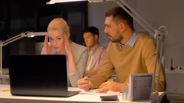 business-team-with-laptop-working-at-night-office