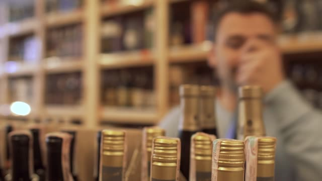 Joyful-guy-taking-a-few-bottles-in-his-hands-and-happily-go-away-Guy-who-choosing-the-wine-in-the-store-is-out-of-focus-