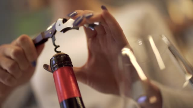 Close-up-of-female-hands-uncorking-a-bottle-of-wine-Girl-uncorking-the-wine-with-a-corkscrew-