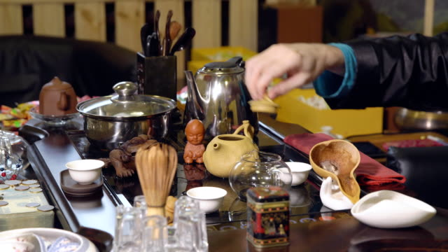 Chinese-traditions-Master-pours-tea-from-a-glass-teapot