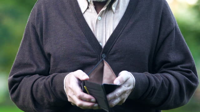 Sad-retired-man-showing-empty-wallet-before-camera-miserable-pension-payments