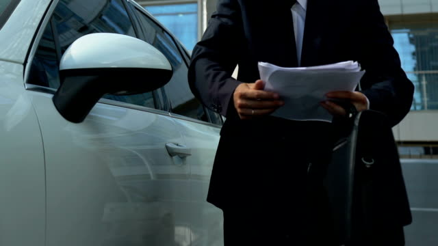 Male-boss-solving-business-issues-on-smartphone-near-vehicle-holding-documents