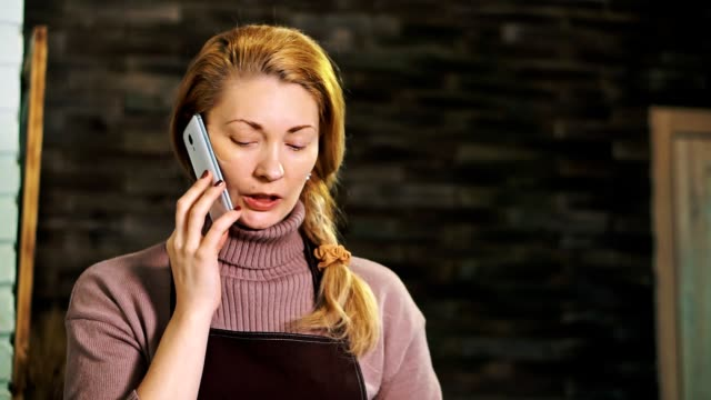 Woman-florist-behind-the-counter-talking-on-the-phone-and-looking-at-the-tablet-