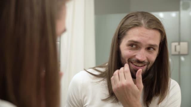 Hombre-en-el-baño-mirando-en-el-espejo-y-tocarse-la-cara