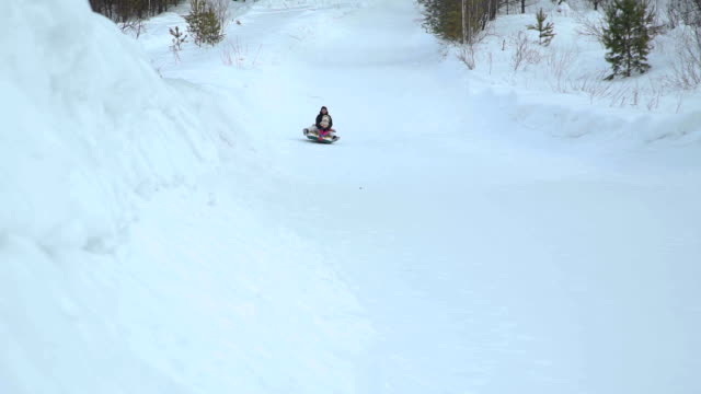 Woman-and-Girl-Riding-Fast-on-a-Sledding-Tubing