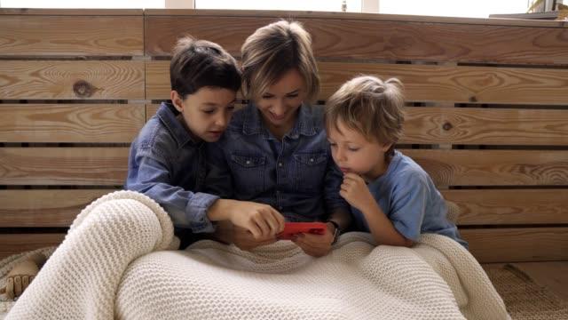 Junge-kaukasische-Frau-mit-zwei-Kind-spaßen-mit-Smartphone-entspannen-auf-der-Couch-glückliche-Jungs-genießen-Zeit-zu-Hause-mit-Mama-zu-verbringen-Videospiele