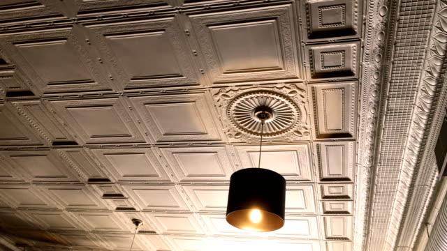 Overhead-golden-light-in-victorian-restarant-against-beautiful-ceiling