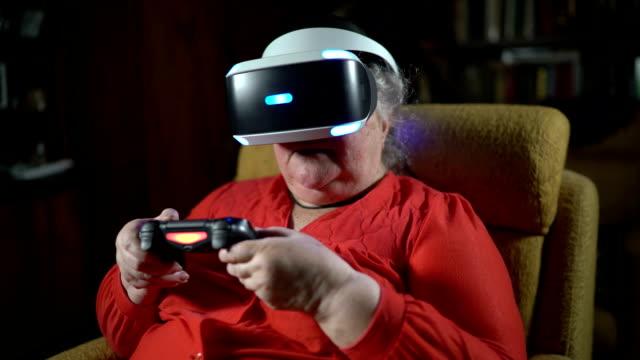 Anciana-delante-de-pantalla-utiliza-VR-auriculares-y-controlador-de-juegos-inalámbrico