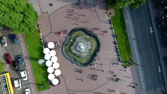 An-aerial-shot-of-a-fountain-on-an-avenue-along-which-people-walk