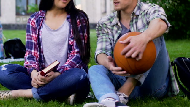 Girl-with-book-guy-with-basketball-ball-sitting-grass-and-talking-relationship
