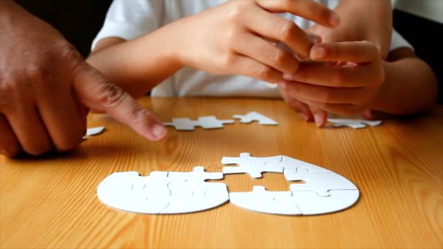 Niña-y-jugar-rompecabezas-con-foco-selecto-de-la-madre-por-parte-de-la-familia-asiática-baja-profundidad-de-campo
