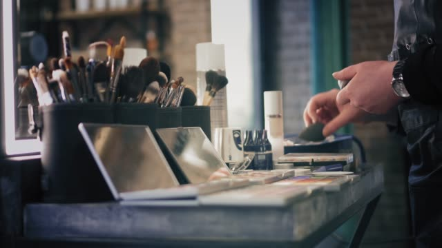Brush-sets-and-shadow-palettes-for-make-up-on-the-table-in-beauty-salon