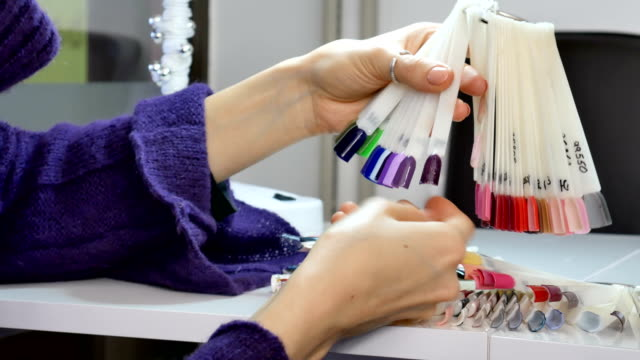 Woman-Hands-with-Natural-Manicure-and-Short-Nails-Choosing-Ultraviolet-Nail-Sample-from-Palette-