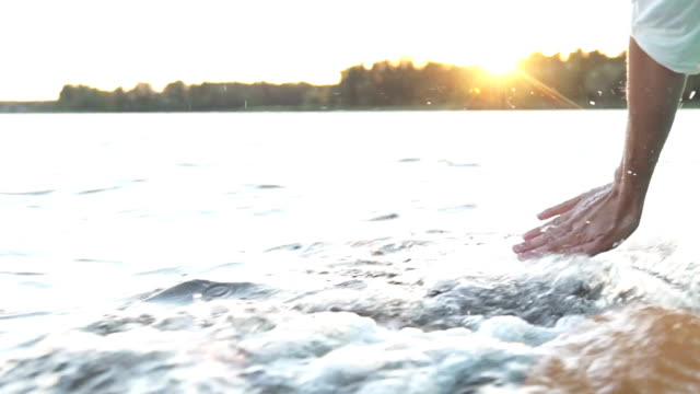 At-sunset-close-up-the-hand-of-a-girl-moving-through-the-water