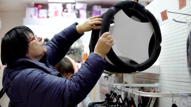 Mujer-madura-en-elige-un-ajuste-suave-para-el-volante-de-un-coche-
