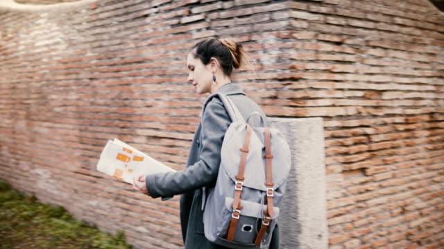 Cámara-sigue-a-mujer-joven-viajero-emocionado-con-las-ruinas-de-antiguo-ladrillo-rojo-histórico-de-expolring-mochila-de-Ostia-Italia-