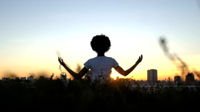 Señora-afroamericana-practicando-yoga-sentado-en-posición-de-loto-puesta-de-sol-en-la-ciudad-de