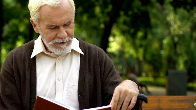 Viejo-arrugado-con-caña-sentado-en-Banco-y-libro-de-lectura-en-el-parque-verde