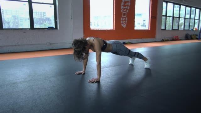 Joven-sano-hermoso-fit-mujer-haciendo-push-ups-de-entrenamiento-en-el-gimnasio-Concepto-de-deporte-fitness-salud-Cámara-lenta-