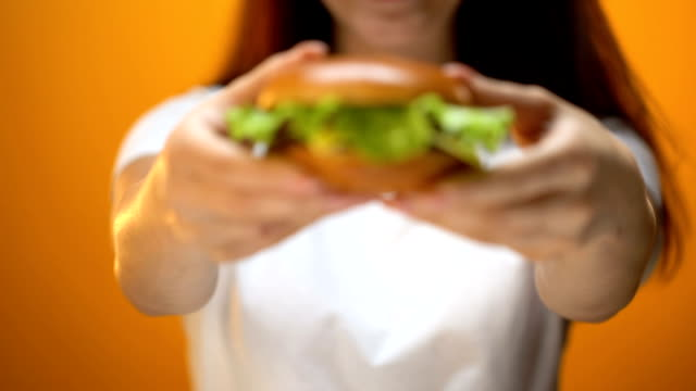 Girl-showing-beef-burger-to-camera-temptation-by-fast-food-unhealthy-eating