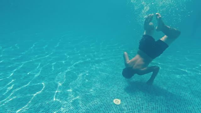 Junger-Mann-schwimmt-unter-Wasser-in-einem-Schwimmbad