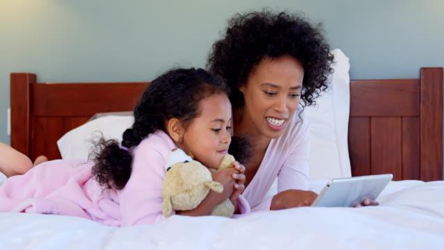 Vista-frontal-de-negro-madre-e-hija-con-tableta-digital-en-cómoda-casa-4k