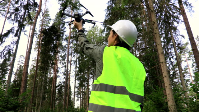 Woman-Worker-with-Drone-Quadcopter-before-take-off-in-forest-Video-forest-inspection