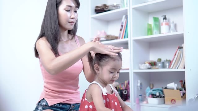 Mother-and-daughter-dress-and-comb-hair-in-the-house-