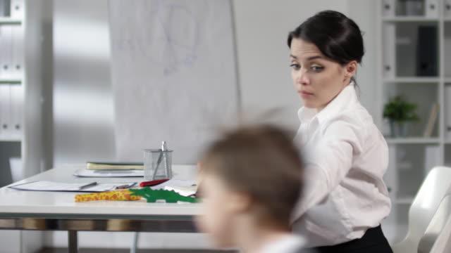 Geschäftsfrau-arbeitet-am-Schreibtisch-während-little-Son-im-Büro-spielt