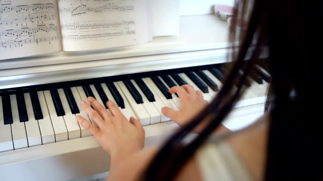 Young-brunette-woman-is-playing-piano-in-bright-room-hand-held